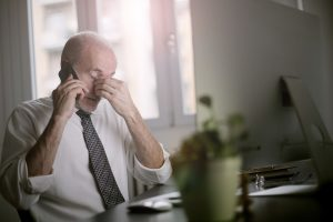 stressed man on the phone, filing a personal injury claim without a lawyer
