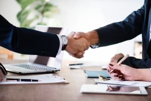 two men in suits shaking hands | personal injury attorney claim requirements